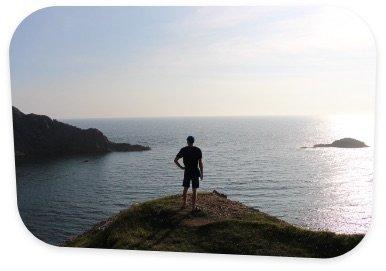 Man stood on cliff overlooking the sea