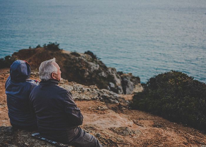 Elderly couple sat on cliff overlooking the sea