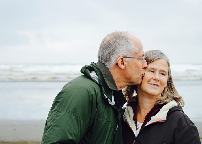 Elderly couple stood on a beach