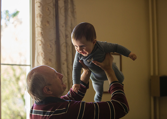 Elderly man holding a baby in the air and smiling