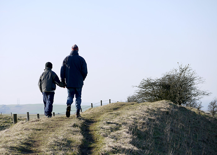 Father and son holding hands and walking in the countryside