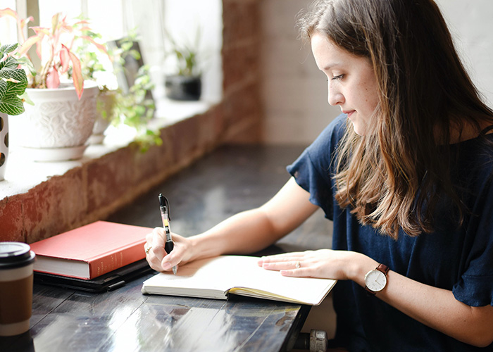 Young woman sat at a desk and writing in a notebook