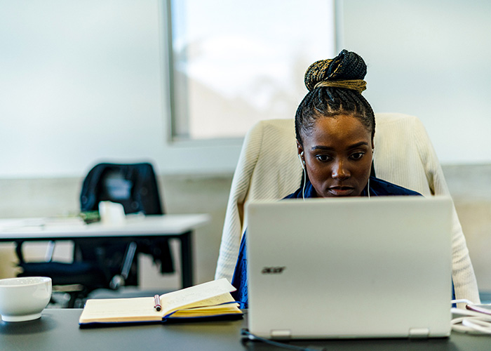 Woman looking at laptop and wearing earphones